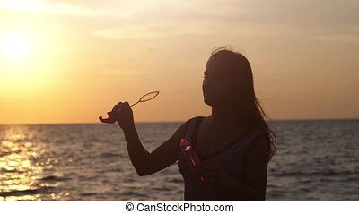 Happy brunette girl blowing soap bubbles on the beach at beautiful sunset in windy weather in slow motion. 1920x1080