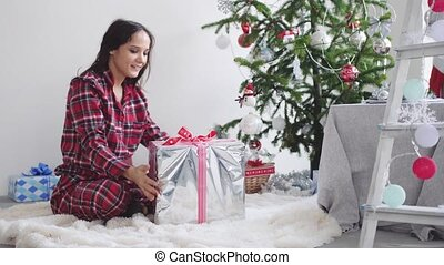 Happy brunette girl comes to fir-tree opens gift by unleashing a festive ribbon at the New Year tree in a decorated beautiful studio. slow motion. 3840x2160