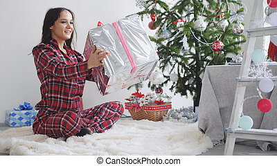 Happy brunette girl holds gift box at the New Year tree in a decorated beautiful studio
