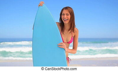 Happy brunette holding a blue surfboard