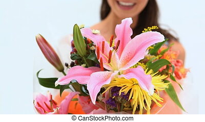 Happy brunette holding a bunch of flowers