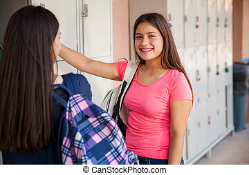 Beautiful high school student and her friend having a good time in school
