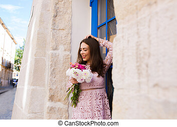 Happy brunette model in short dress holding bouquet of flowers at the city