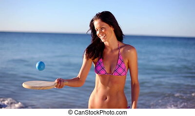 Happy brunette playing with a paddle on the beach