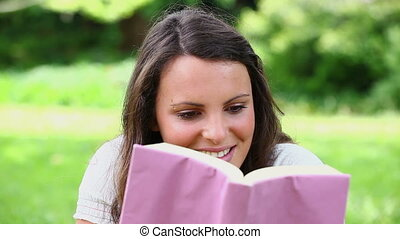 Happy brunette reading a novel in a park