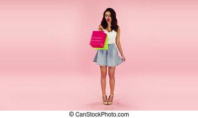 happy brunette shopper on pink background