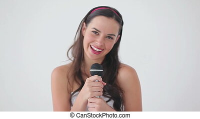 Happy brunette singing into a microphone