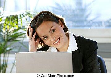 Happy brunette sitting at her desk