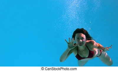Happy brunette waving at camera underwater
