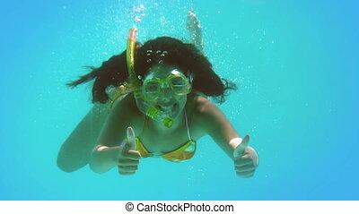 Happy brunette wearing snorkel underwater
