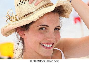 Happy brunette wearing straw hat