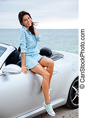 Happy brunette woman and her new car