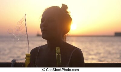 Happy brunette woman blowing soap bubbles on the cruise ship at beautiful sunset in the sea. Slow motion.