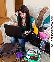 Happy brunette woman choosing resort online