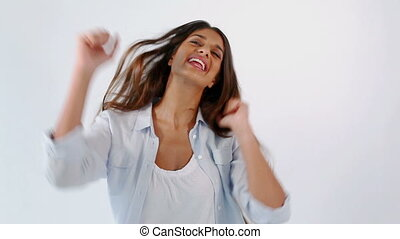 Happy brunette woman dancing against a white background