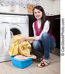 happy brunette woman doing laundry
