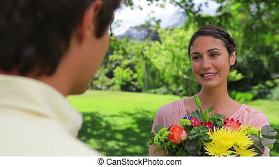 Happy brunette woman holding a bunch of flowers
