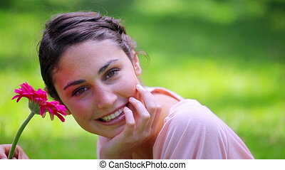 Happy brunette woman holding a pink flower