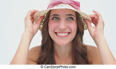 Happy brunette woman holding her hat