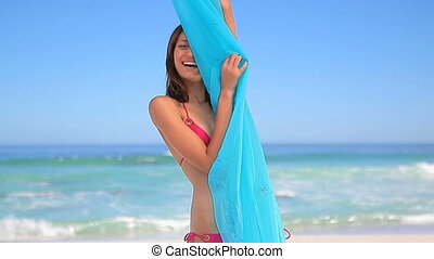 Happy brunette woman holding her sarong on the beach
