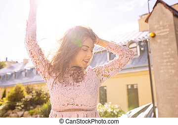 Happy brunette woman in lace dress posing at the street in rays of sun