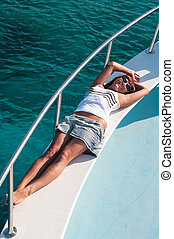Happy brunette woman laying on shipboard of yacht in ...