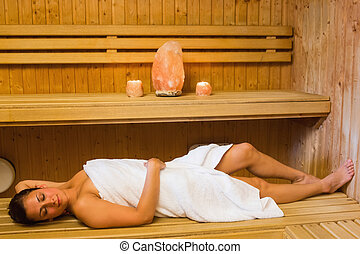 Happy brunette woman lying in a sauna