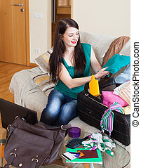 Happy brunette woman packing suitcases