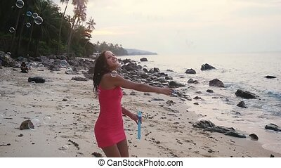 Happy brunette woman playing with soap bubbles on tropical beach at sunset time. slow motion. 1920x1080