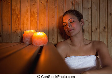 Happy brunette woman sitting in a sauna relaxing by...