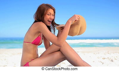 Happy brunette woman sitting on the sand while holding her hat