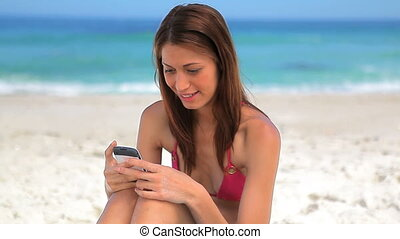 Happy brunette woman sitting while using her cellphone