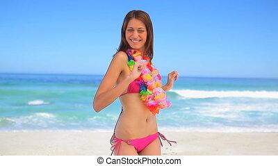 Happy brunette woman wearing a hawaiian necklace on the...