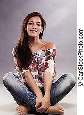 happy brunette woman wearing blue jeans sitting on the floor