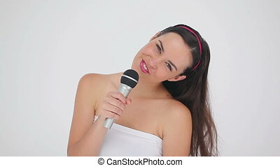 Happy brunette woman with a microphone is singing