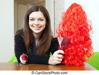 Happy brunette woman with red wig