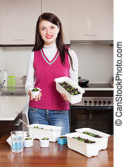 Happy brunette woman with sprouts