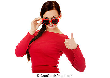 Happy brunette woman with sunglasses in the shape of hearts