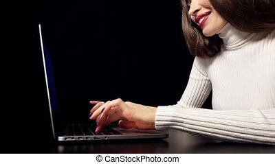 Happy brunette woman working on her laptop against black background.