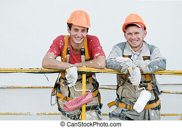 Two happy builder workers facade painters of high-rise building with rollers