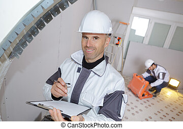 happy builder holding clipboard while working indoors