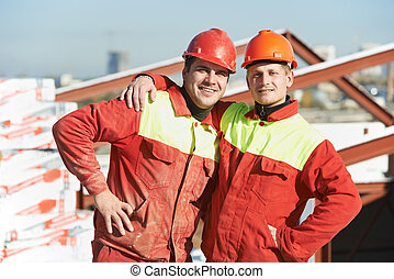 happy builder workers at construction site