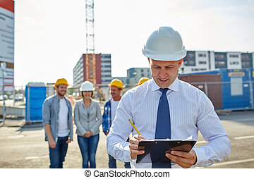 happy builders and architect at construction site -...