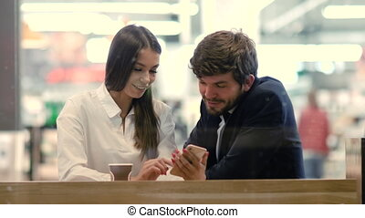 Happy business couple talk laugh looking at smartphone in a mall.