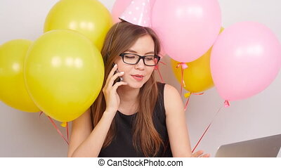 Happy business girl celebrating in the office talking on phone