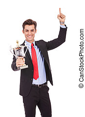 Happy business man holding a trophy
