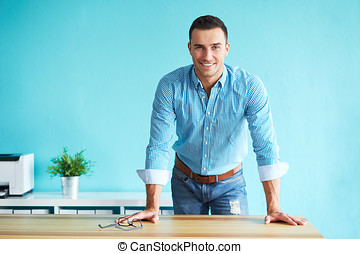 Happy business man leaning on a table in the office