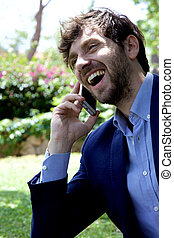 Happy business man on the phone in park laughing
