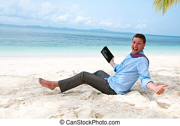 Happy business man sitting and working on the beach with tablet computer