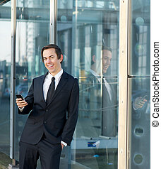 Happy business man smiling outdoors with cellphone